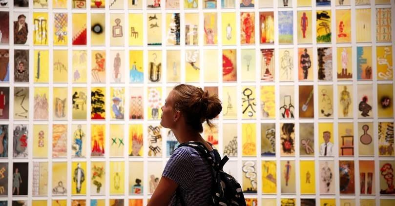 "A woman with a backpack walks through the exhibition ""Rendering the Unthinkable: Artists Respond to 9/11."" Dozens of small artworks are displayed on the wall in front of her."