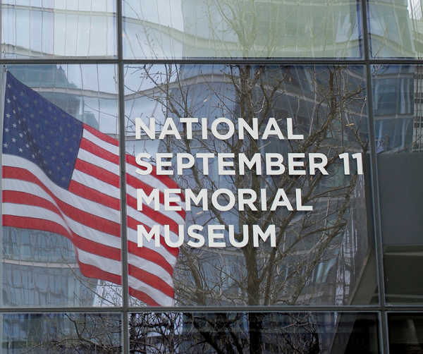 "A sign on the Museum reads ""National September 11 Memorial Museum."" An American flag reflects off the glass that the sign is displayed on."