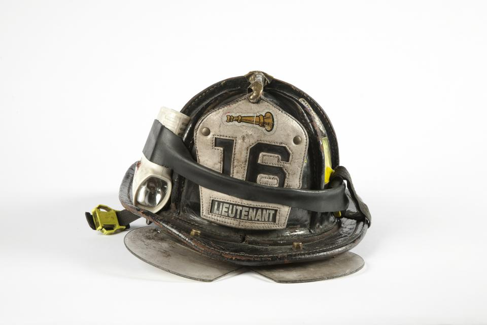 A black and white firefighter helmet with the number 16 and the word lieutenant on it is displayed on a white surface at the Museum.