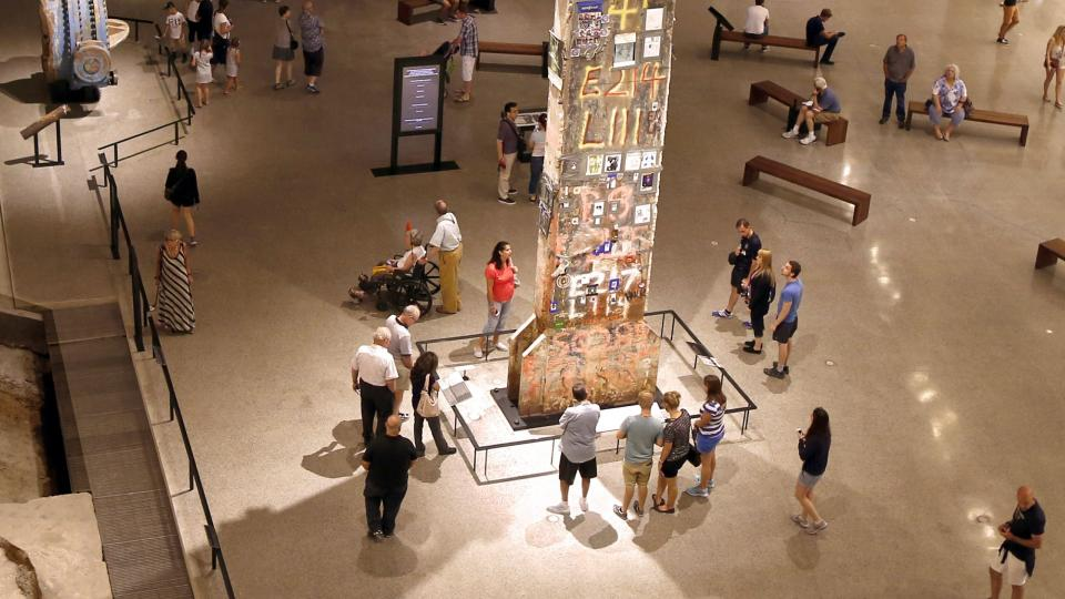 The Last Column towers over Museum visitors gathered around it. The thirty-six-foot-tall steel beam is covered in pictures and tributes left by recovery workers at Ground Zero. Off to the left, visitors observe a river water valve that was recovered from under the World Trade Center.