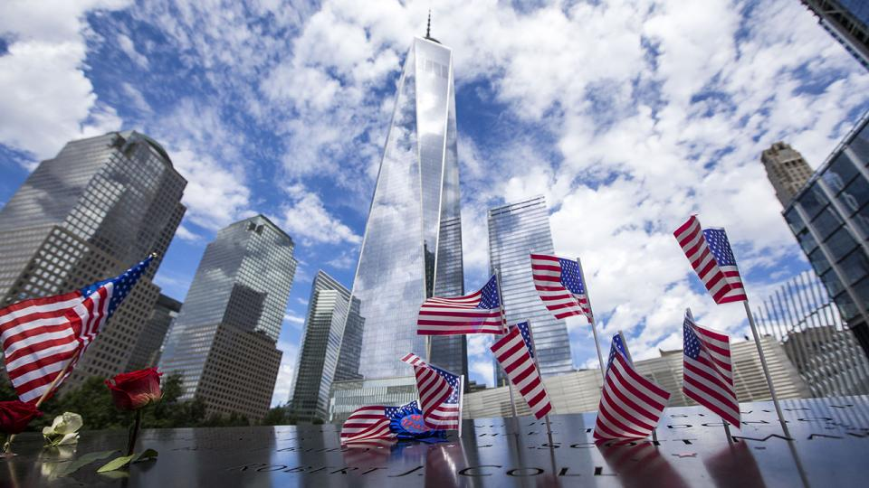 American flags are placed in the bronze parapets as One World Trade soars skyward amid white clouds and blue skies.