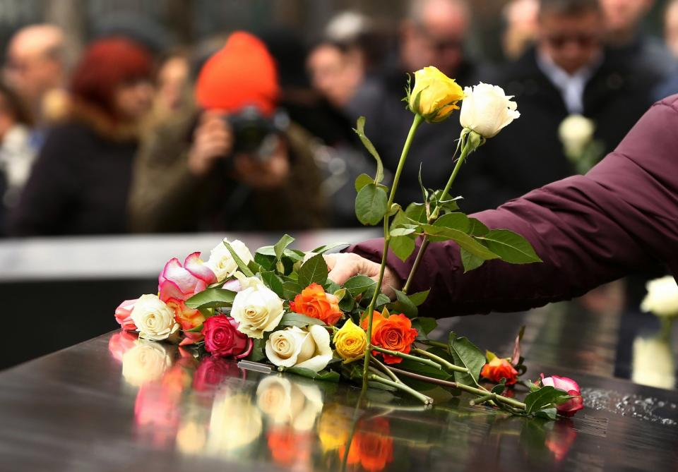 A person's arm is seen placing a bouquet of red, orange, yellow, and whiite roses on a bronze parapet at the Memorial.