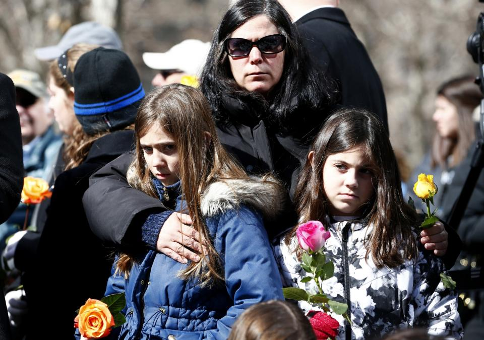 A woman embraces two girls as they stand during a moment of silence on Memorial plaza. The three of them are holding multicolored roses.