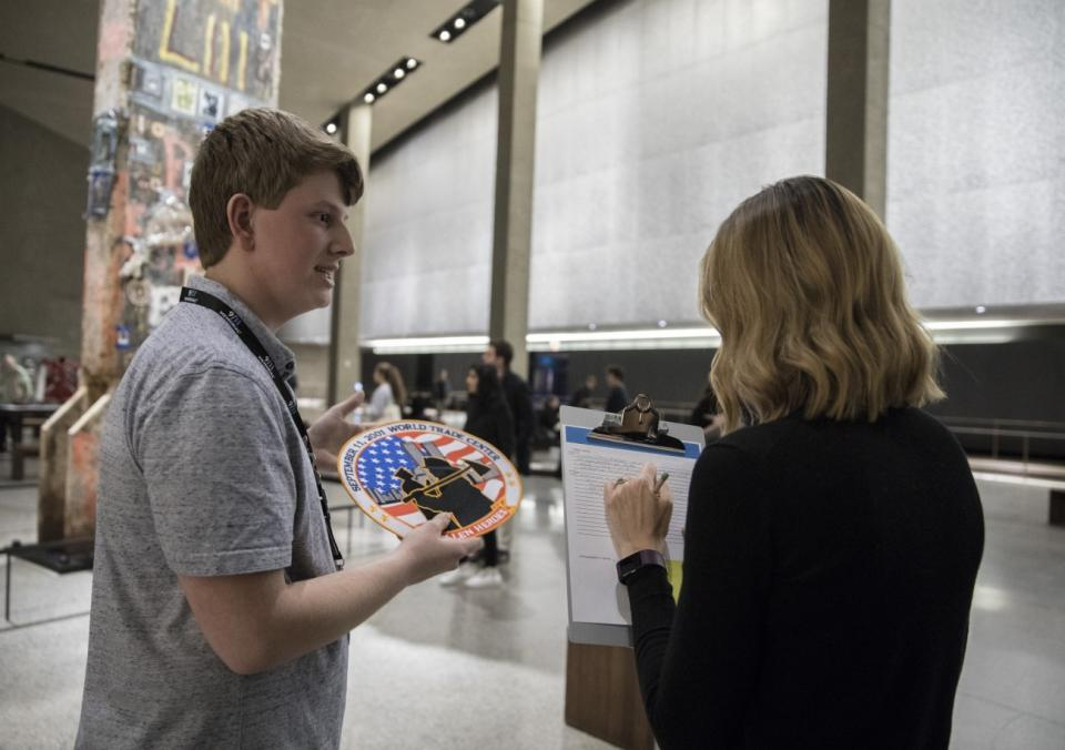 John Spade, son of 9/11 survivor and museum docent, Bill Spade, speaks to a woman with a clipboard beside the Last Column in Foundation Hall. He is holding up a large patch dedicated to the heroes of 9/11.