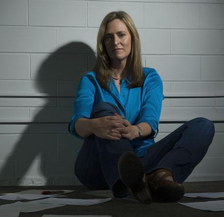 A woman sits with crossed legs in front of a white wall.