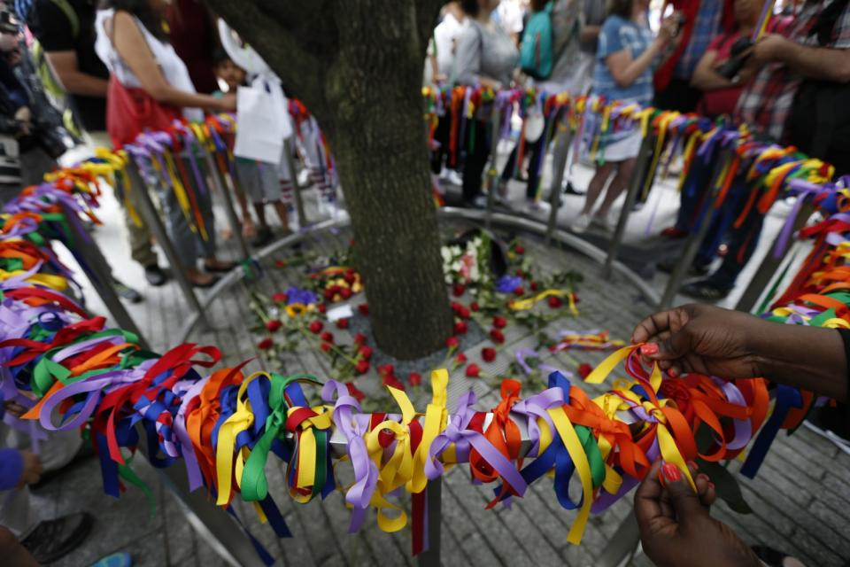 People tie multicolored ribbons on a railing surrounding the Survivor Tree to honor victims of the Orlando nightclub attack.