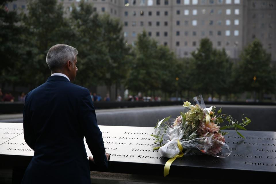 Shadiq Khan, the mayor of London, looks out at a reflecting pool at the 9/11 Memorial. A bouquet of flowers sits on the bronza parapet beside him.