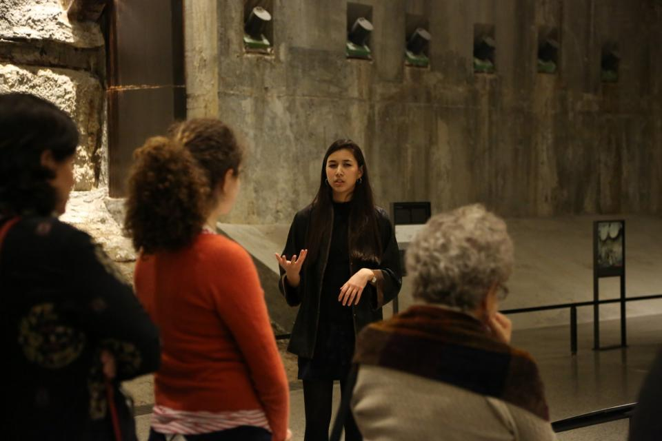 9/11 Memorial Museum ambassador Annalee Tai leads a Museum tour beside the slurry wall. Three visitors are in the foreground listening to her.