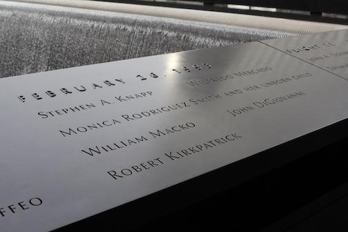 The names of the six victims of the 1993 bombing are seen on a bronze parapet beside a reflecting pool on the 9/11 Memorial.