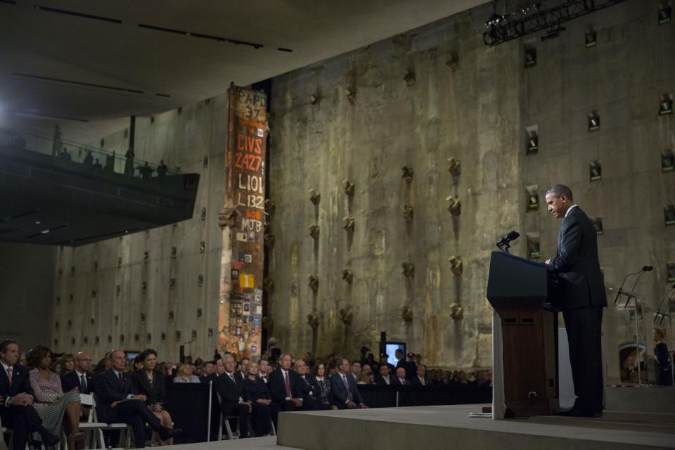 President Barack Obama speaks at a podium during the 9/11 Memorial Museum dedication ceremony. Audience members watch him beside the slurry wall and Last Column.