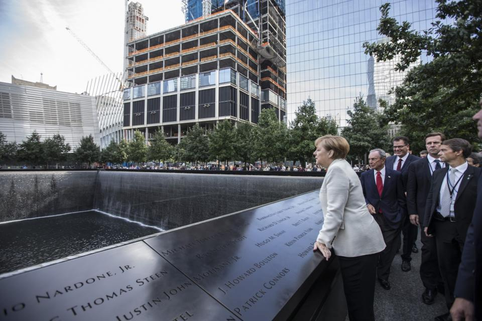 German Chancellor Angela Merkel looks over the south pool at the 9/11 Memorial. Michael Bloomberg and other visitors stand beside her.