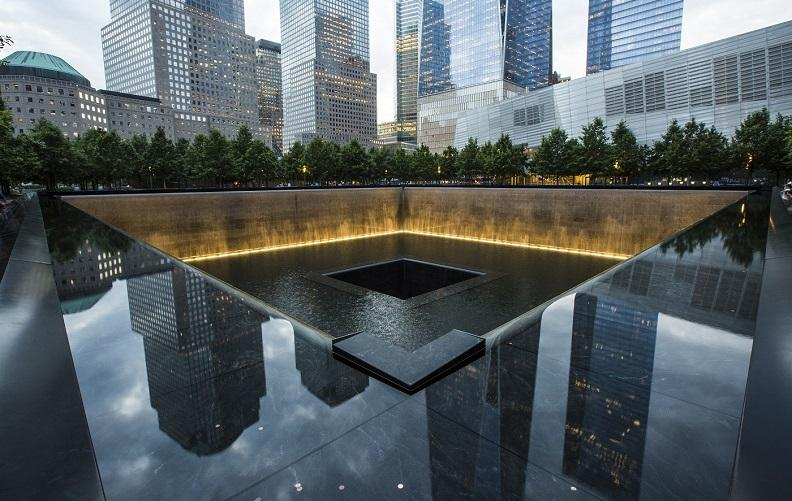 The glare of an overcast, late-afternoon sky reflects off the water within the Memorial Pool.