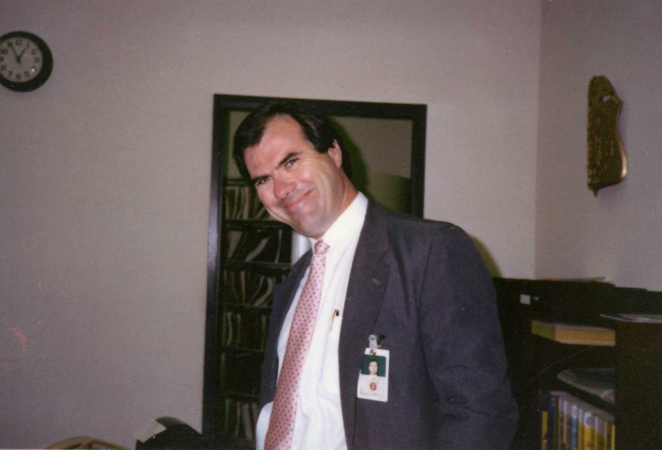 A man wearing a suit and tie and a professional badge grins with his head tilted to the side in an office.