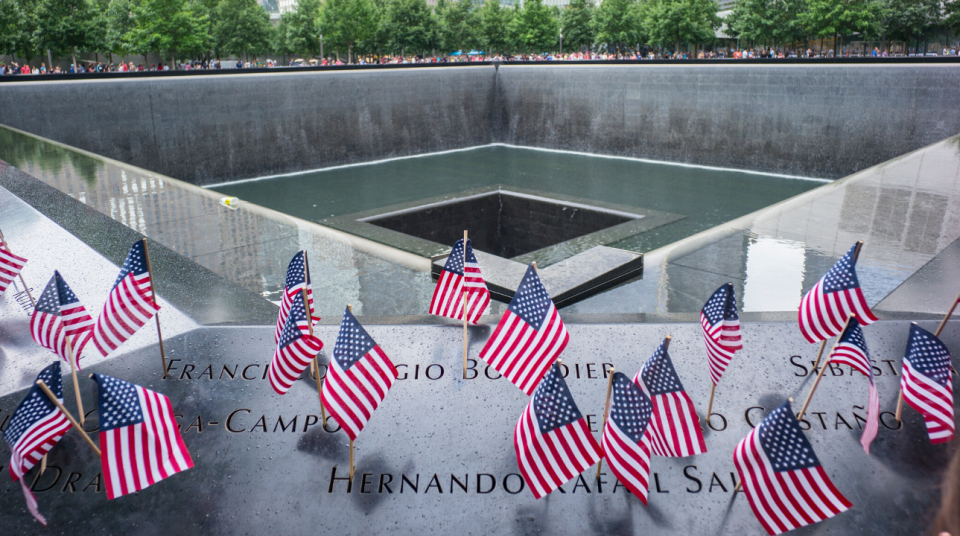 American flags are placed in the names of the 9/11 Memorial parapets. The center of the Memorial pool is visible behind them.