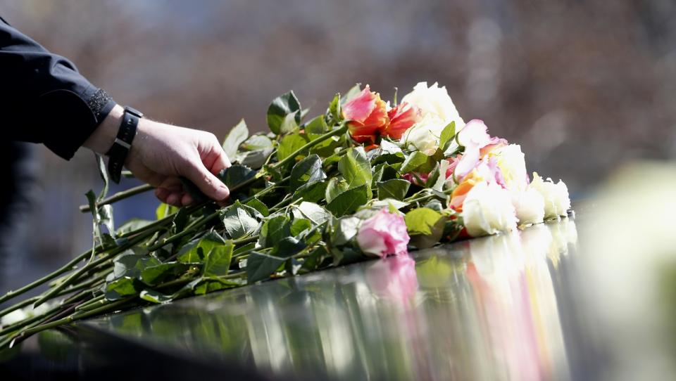 A hand places a long-stemmed rose on the memorial parapet.