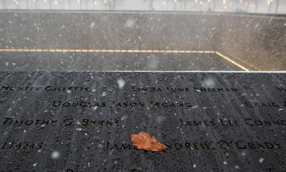 Snow falls on the 9/11 Memorial while a yellow leaf rests on the bronze parapets.
