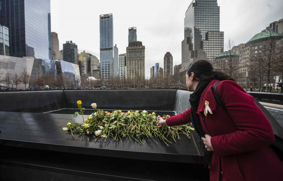A woman in a red winter coat place a rose atop other flowers left on panel N-73 of the 9/11 Memorial's North Pool to commemorate the victims of the 1991 attack on the World Trade Center.