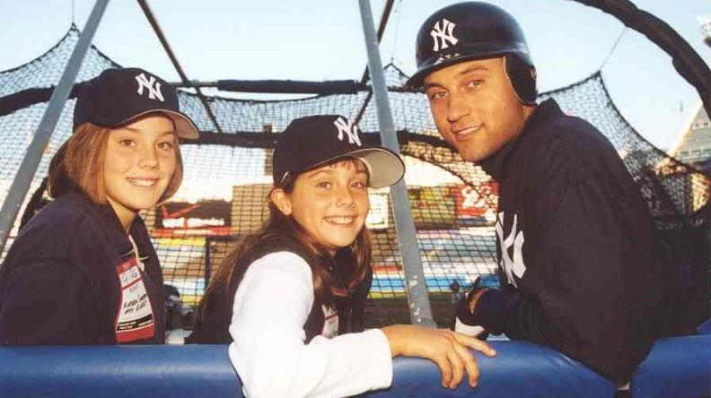 Two young women sit with New York Yankee Derek Jeter on a bench, where they are turned around to pose for the camera behind them.