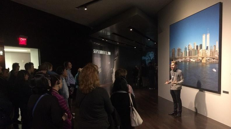 In this photograph, an interpretive museum guide stands before a blown-up photograph of the New York skyline pre-9/11, giving a tour to a group of museum visitors, who listen through headsets.