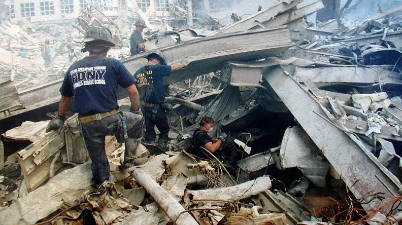 Two firefighters in masks and navy blue T-shirts wade through the rubble and twisted steel at Ground Zero while another descends into a cravasse.